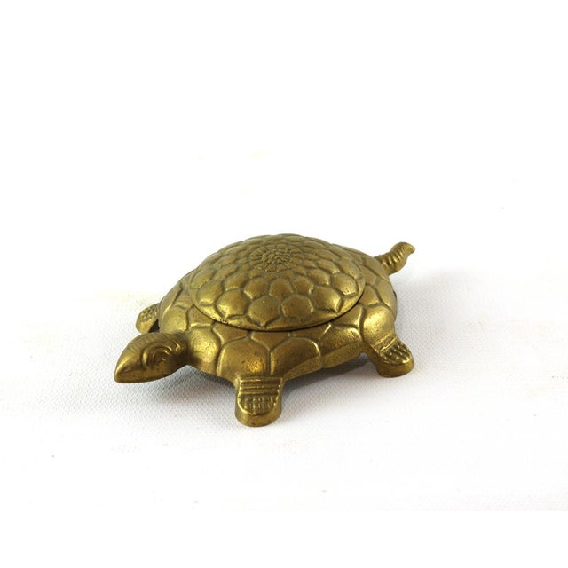 This vintage brass turtle trinket box has a removable lid on its shell which reveals a small circular space inside. Marked...