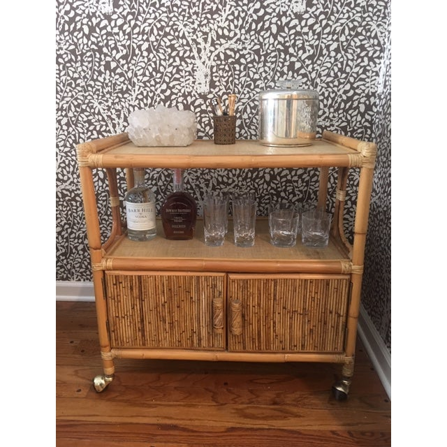 Awesome rattan bar cart with caning on shelves. Great storage down below. Wheel it around to create a bar in any room of...