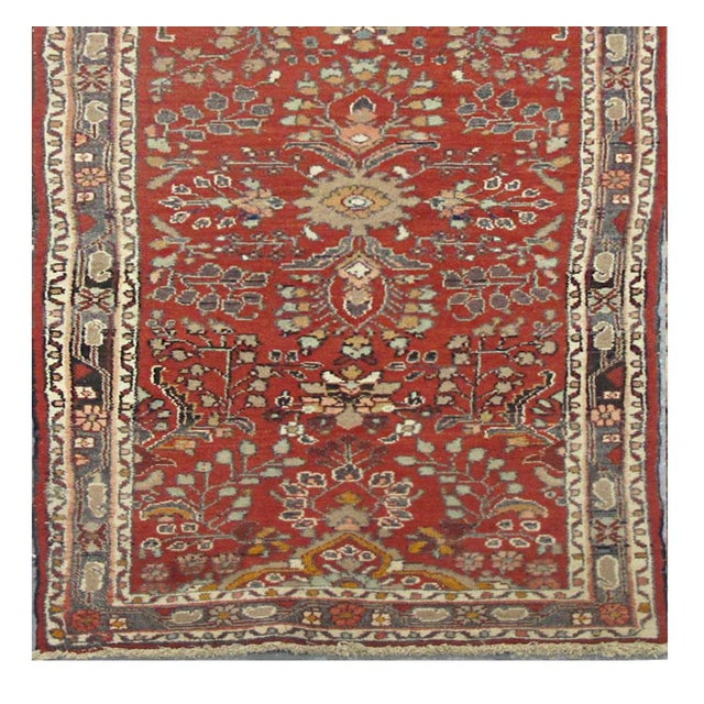 This beautiful rug is hand made, made in Iran. It features a pattern in a vibrant combination of red, navy blue, grey....
