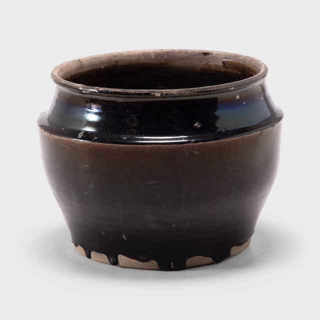 As though slicked with oil, a thick blue-black glaze spills over this squat kitchen vessel, pooling at the angular...