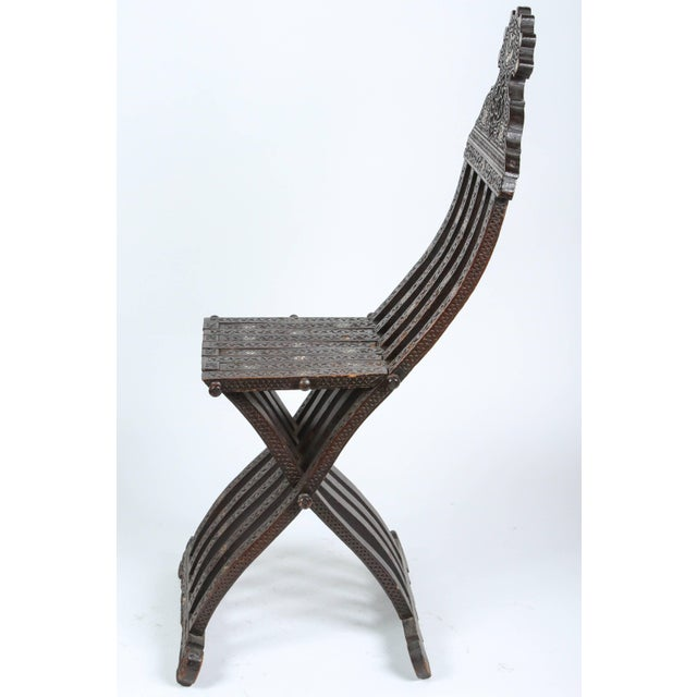 Middle Eastern Syrian wood folding chair with intricate foliate carving and mother-of-pearl inlays. Inlaid with mother-of-...