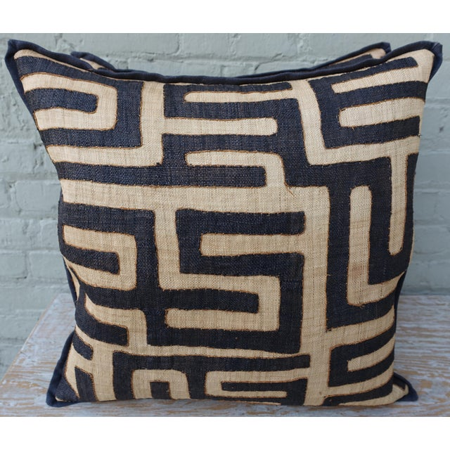 Large square custom African Tribal Kuba cloth pillows. Black and tan pattern with contrasting orange stitching. Black...