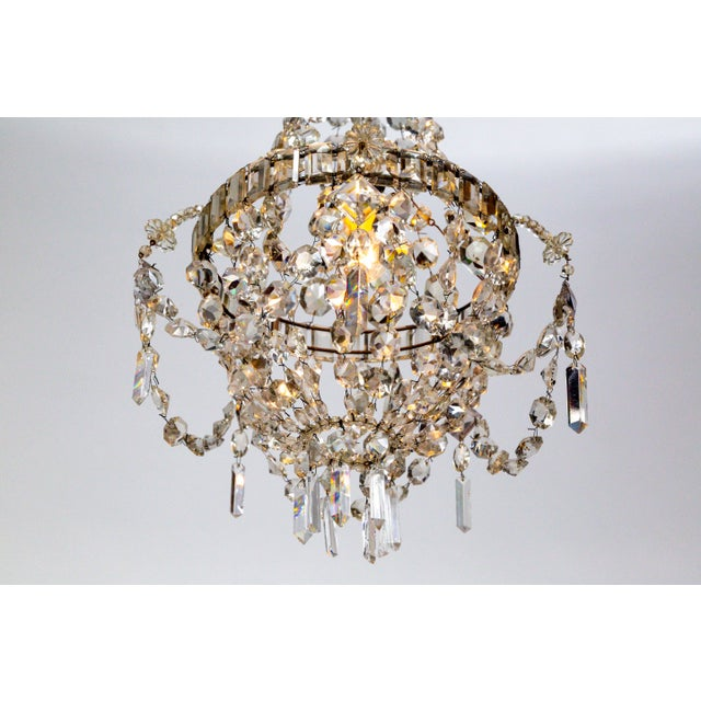 An exceptional French Regency chandelier delicately composed entirely of highly prismatic, extremely sharp, cut crystals...