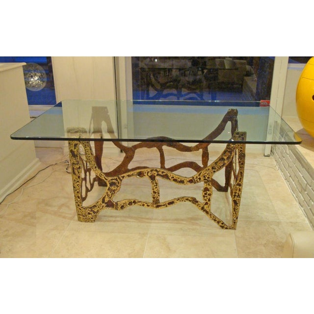 Mid-century modernist dining table featuring a four-sided base in sand cast bronze featuring an open fretwork design with...