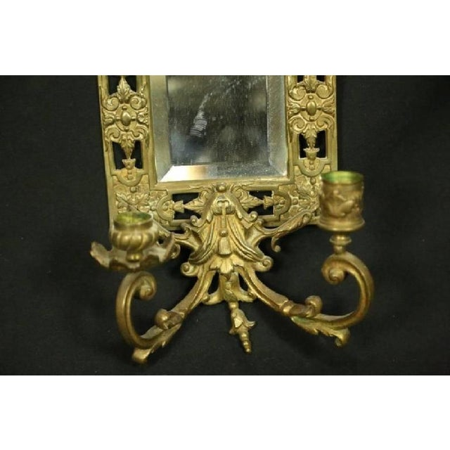 A matched pair of American Neoclassical Revival Bradley & Hubbard brass candle sconces with original bevelled mirrors and...