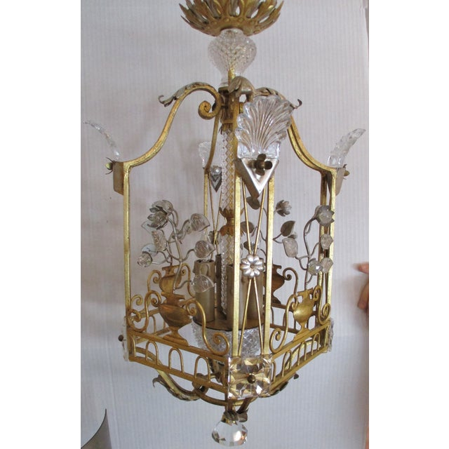Maison Bagues style crystal and iron gold and silver leaf lantern chandelier. The lantern is four sided with four...