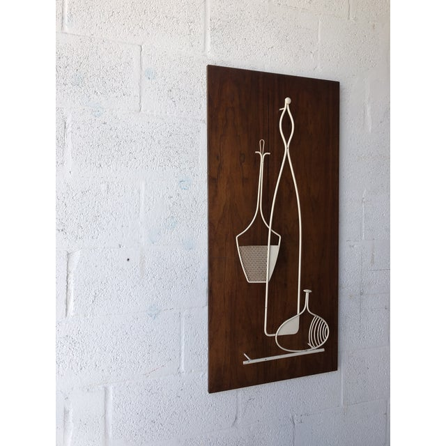 Vintage 1960s Mid Century Modern Wall Sculpture. Features a metal sculpture floating on Walnut Board with a beautiful...
