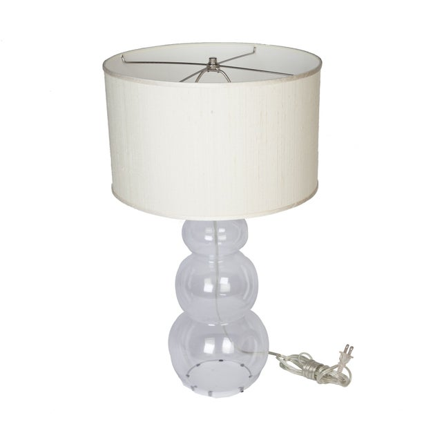 This clear glass lamp base comes with a natural-colored silk shade. 100 watts max and a 3-way switch. It's sure to...