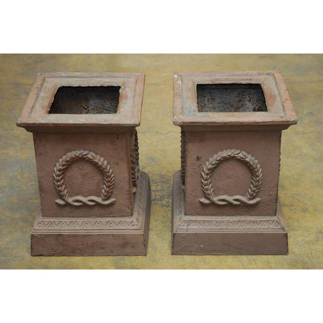 Handsome pair of cast iron square pedestals or garden urns made in the Neoclassical taste. Featuring an iron wreath...