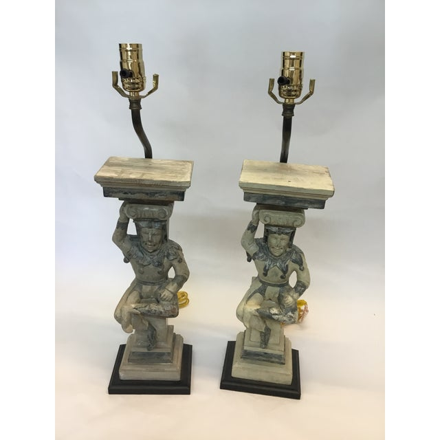 Hand carved wooden court jester lamps on a square base Hand painted antique finish Jesters on sitting position Condition:...