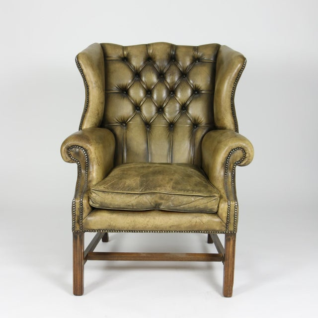 Handsome mahogany and original tufted green leather wing chair with loose cushion. Georgian style leg and brass nailhead...