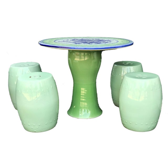 Celadon glazed hand painted porcelain table with blue-and-white dragon motif for good luck and four large garden stools....