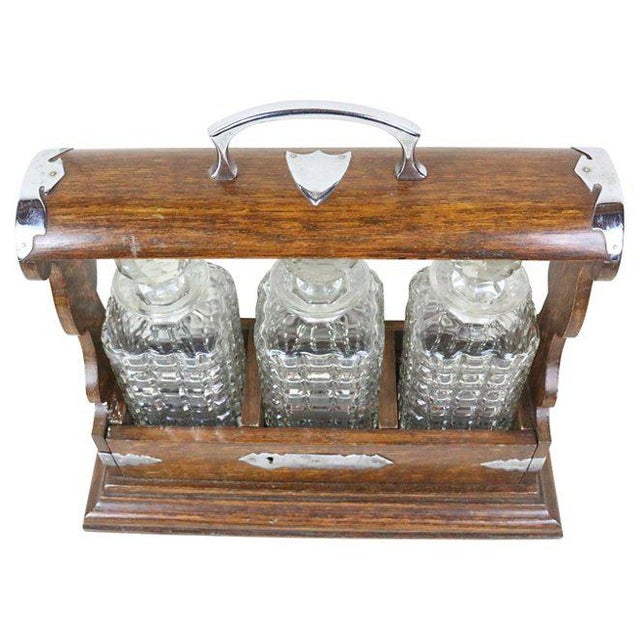 English tantalus dating from the end of the 19th century. Includes three cut-glass liquor decanters set into an oak and...