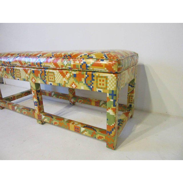 An upholstered bench with colorful, 1980s patterns in oil cloth with lower stretchers, from the period, well-crafted and...