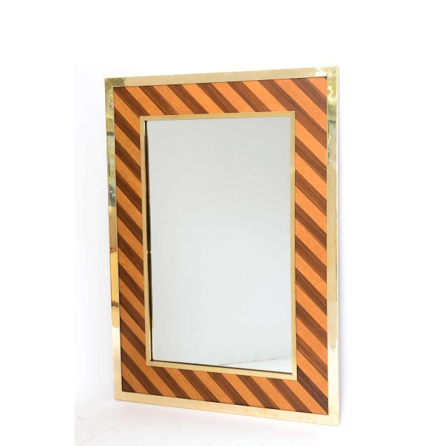 Substantial 1970s wall mirror in the style of Mastercraft. Heavy polished brass frame outlines diagonal bands of black...