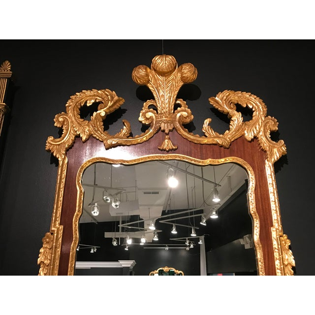 Trimmed in gilded gold carved leaves and flowers with a plume on the top center. Made in the 1960s
