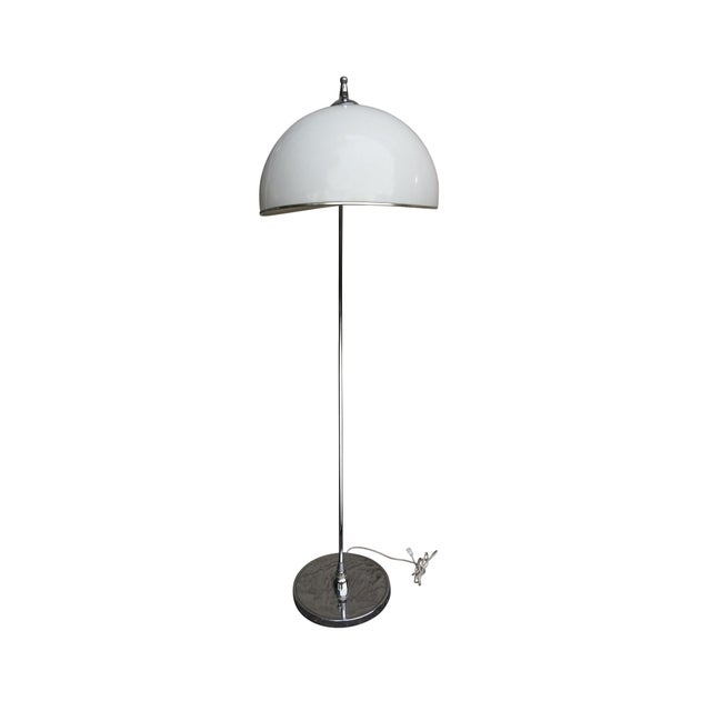 A 1950's mid century modern chrome floor lamp with a plastic bubble shade. The chrome column is attached to the round base...