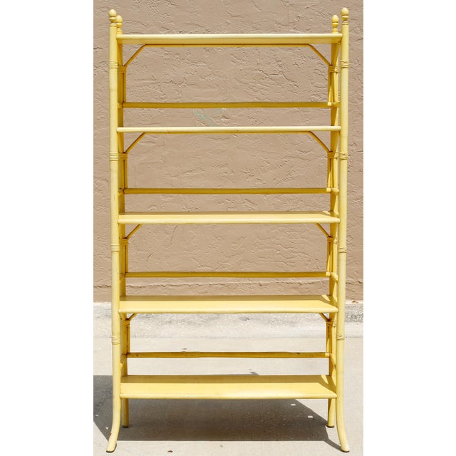 A vintage, pale yellow rattan bookcase or etagere with five shelves. Good vintage condition; minor wear consistent with...