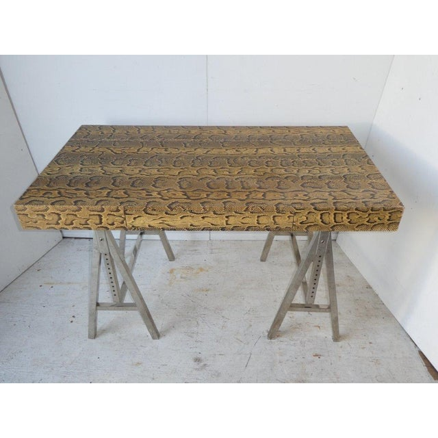 20th century desk covered in snakeskin on a pair of polished steel adjustable sawhorse legs, single drawer, sturdy.