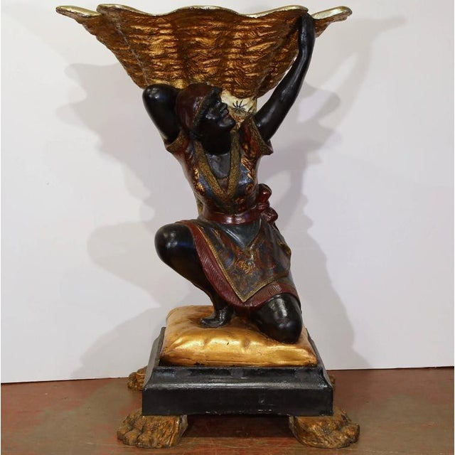 This large antique polychrome Blackamoor figure Jardiniere from Italy, circa 1820, features a young woman carrying a large...