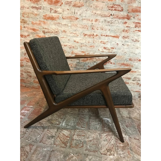 An original Poul Jensen for Selig mid-century lounge chair. Features a walnut stain on beech sculpted frame with newly...