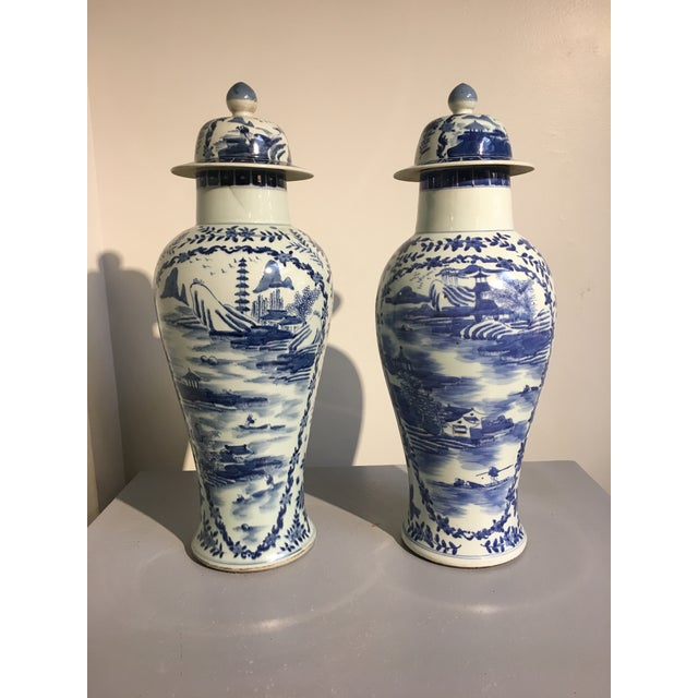 A near pair of tall and elegant blue and white painted porcelain baluster jars with lids, China, circa 1900. The jars of...