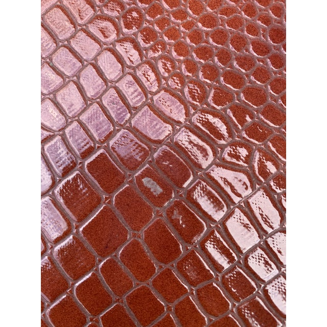 Chic custom wrapped parsons table in a rust colored crocodile textured vinyl.