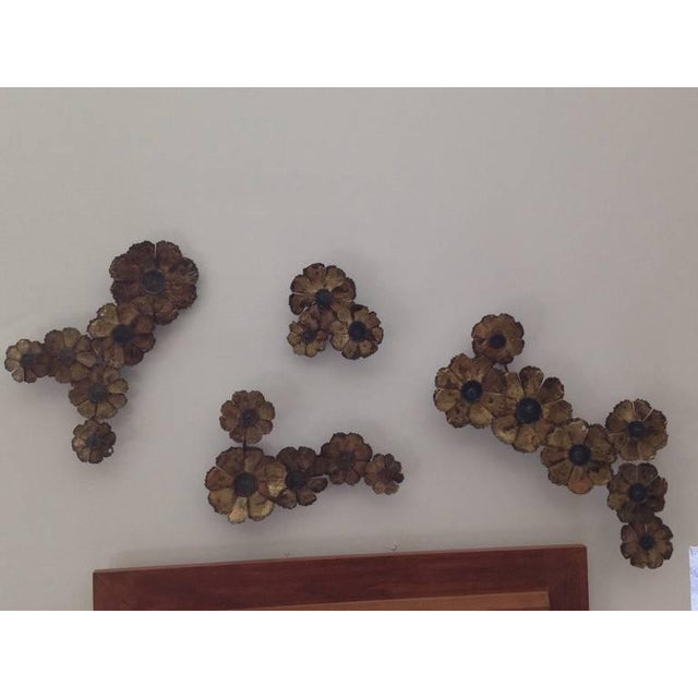 Four unique sculptures in torch cut brass flowers motif. Can be hung in many variations to wall. Dimensions of largest: 21...
