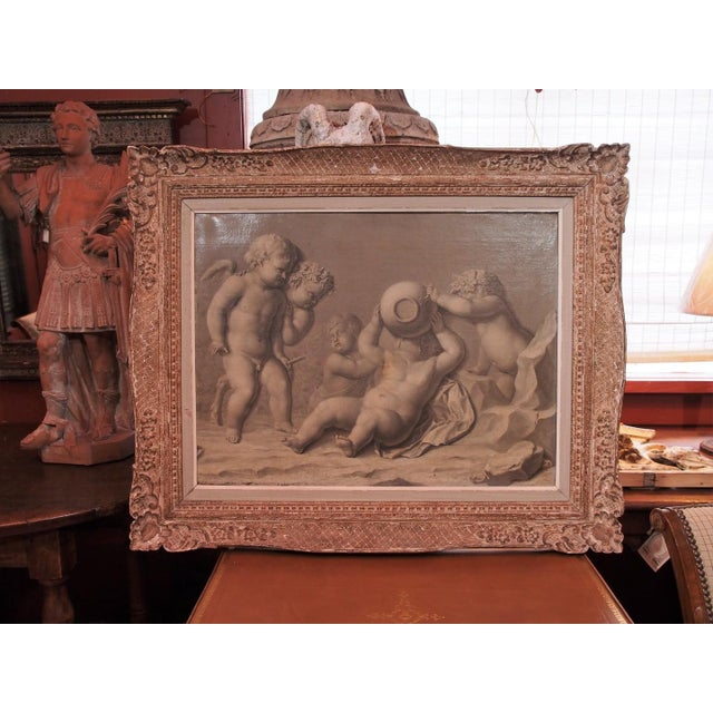 Large canvas grisaille painting of cherubs, one with wings and hooves. Two of them are crowned with a wreath of grape...