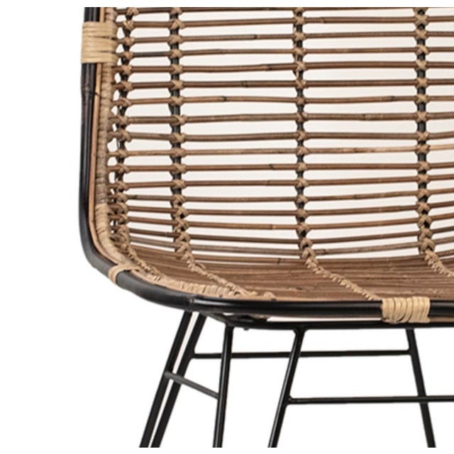 Natural rattan dining chair with distressed finish black tube frame and iron legs. Slight natural differences in tones,...