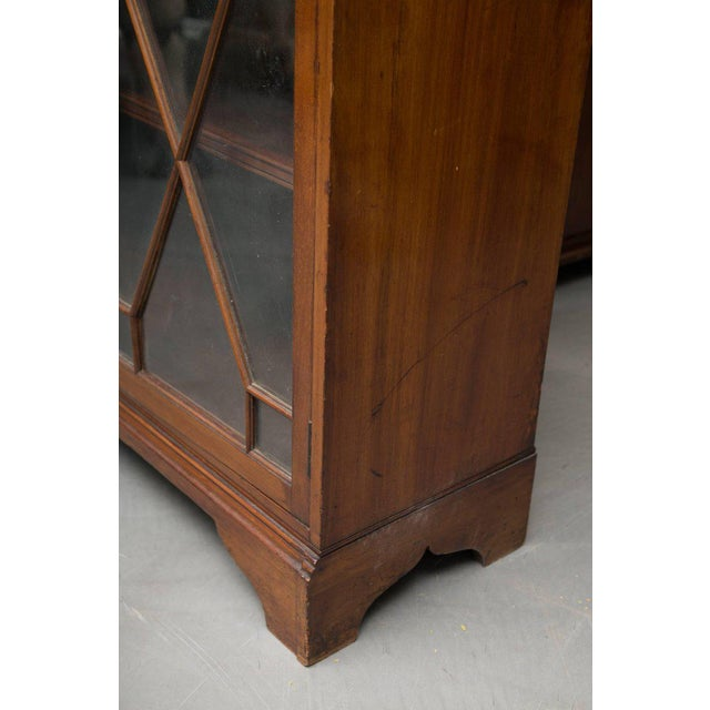 This dwarf English mahogany bookcase has a small shaped cornice above two fixed sections, top and bottom, each with a pair...