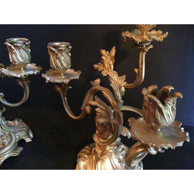 This pair of bronze candelabras are high quality fire gilded with three candle cups each. These 19th century sculptural...