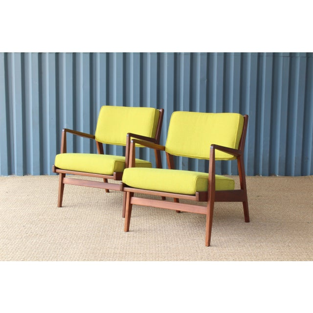 Pair of armchairs designed by Jens Risom. The pair feature solid walnut frames that have been refinished. They have been...