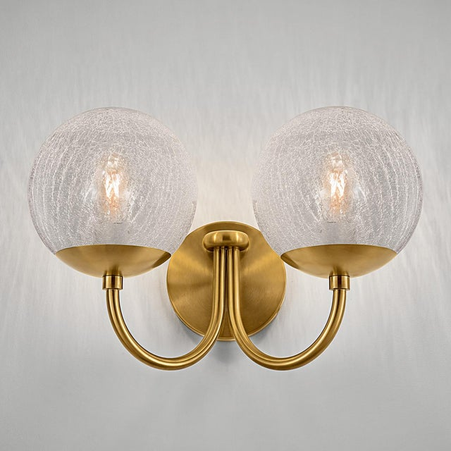 A brushed brass wall light with two arms each with a crackled glass globe. The glass has an integral threaded metal fixing...