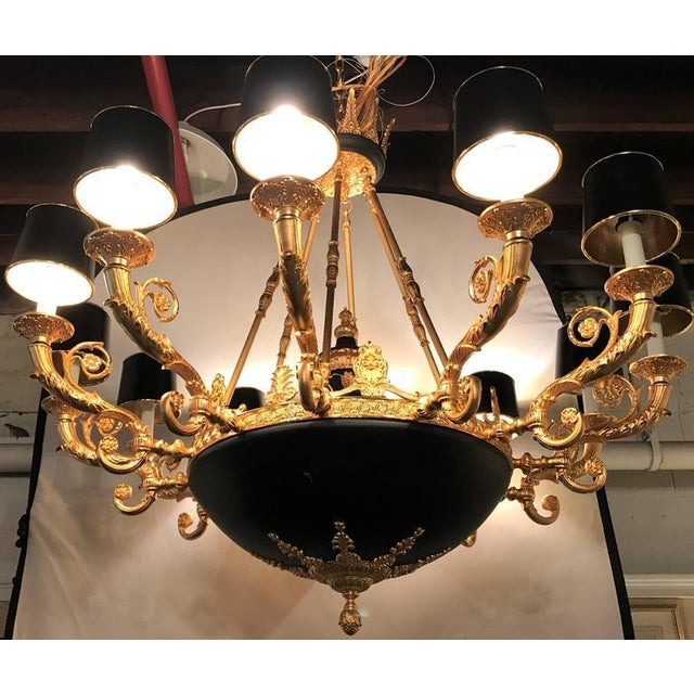 An Empire style twelve-arm chandelier with bronze and ebony high lights. Having a 76 inch chain and matching canopy, this...