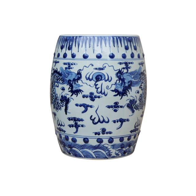 A traditional blue and white hand painted garden stool decorated with two 'contending dragons', facing each other they are...