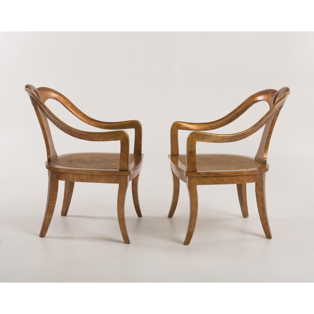 A pair of antique spoon back or Roman arm chairs in a mottled gold finish. The chairs have a wonderful mottled gold...