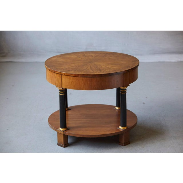 Very fine round Empire style two-tier walnut side or end table with one drawer by Baker Furniture, circa 1970s. Sunburst...