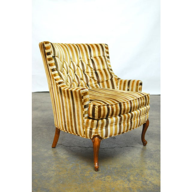 A pair of barrel back club chairs featuring a plush striped velvet upholstery and made by Silvercraft Furniture Co from...