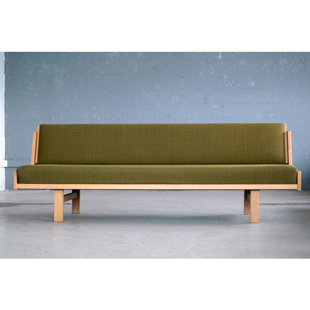 Hans Wegner's iconic daybed designed in 1954 and produced by GETAMA in Denmark. The daybed is made from oak veneer raised...