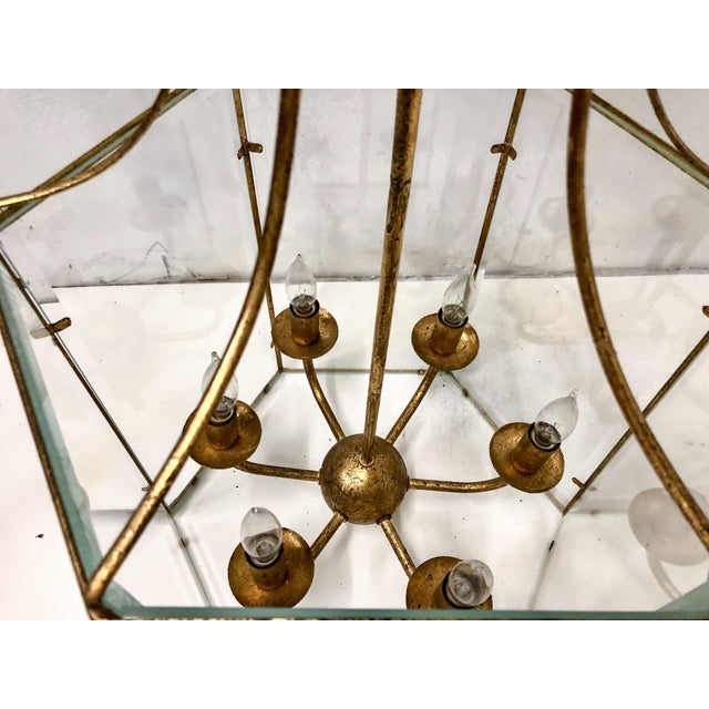 Gilt metal lantern style chandelier. Each panel has beveled glass. There are 6 arms that support 40 watt bulbs. Faux...