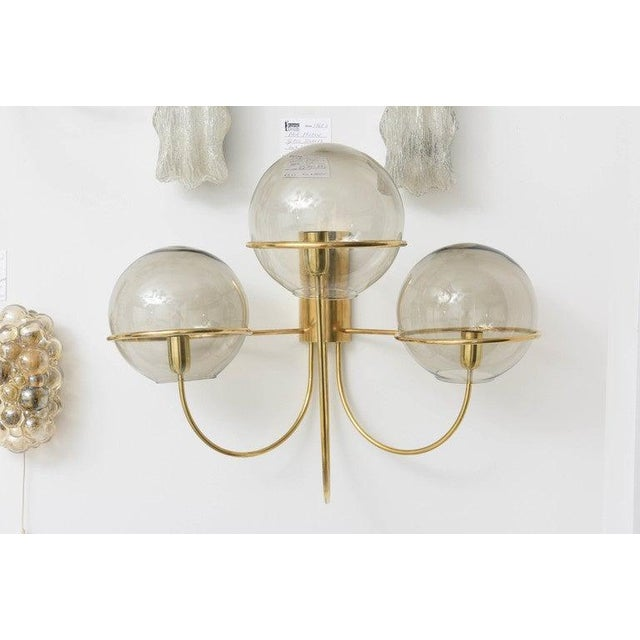 These amazing large-scaled Mid-Century Modern wall sconces in polished brass with smoked-glass globes were produced by...