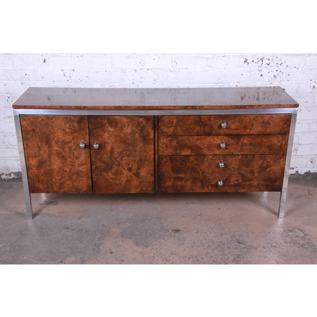 Offering an exceptional mid-century modern burl wood and chrome sideboard or credenza by Tomlinson Furniture. The...