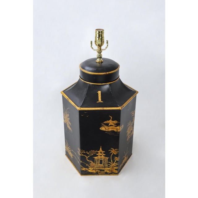This vintage hexagonal tea caddy lamp is painted predominantly black, with gold accents featuring eastern landscapes. The...