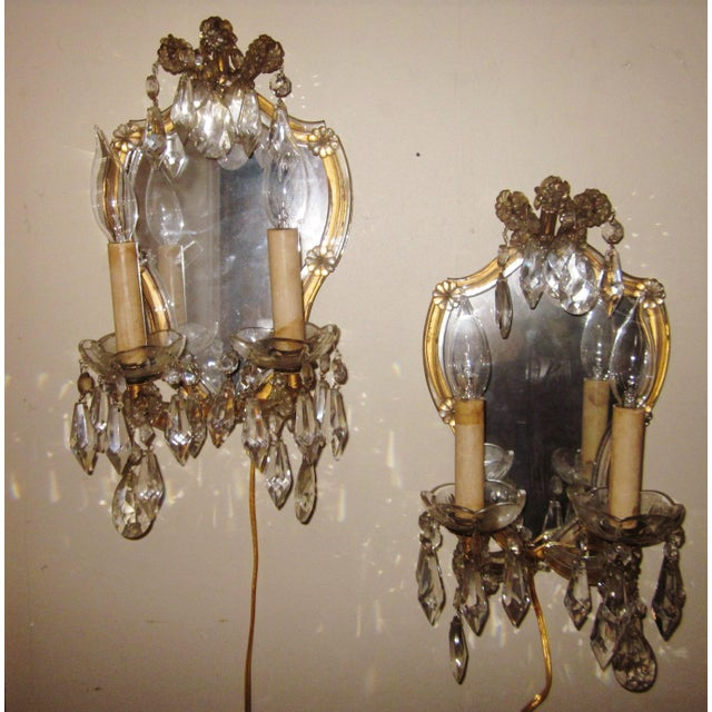 This is an elegant yet playful pair of 1920s French sconces in the traditional Louis XV style, with a mixture of chic...