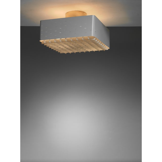 A white lacquered model 9068 Paavo Tynell ceiling lamp for Idman. This flush mount has twin dot perforations and a frosted...