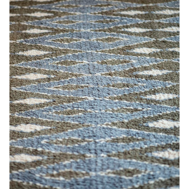 This handwoven Turkish rug has a field with alternating rows of horizontal shaded blue linked diamond lozenges and...