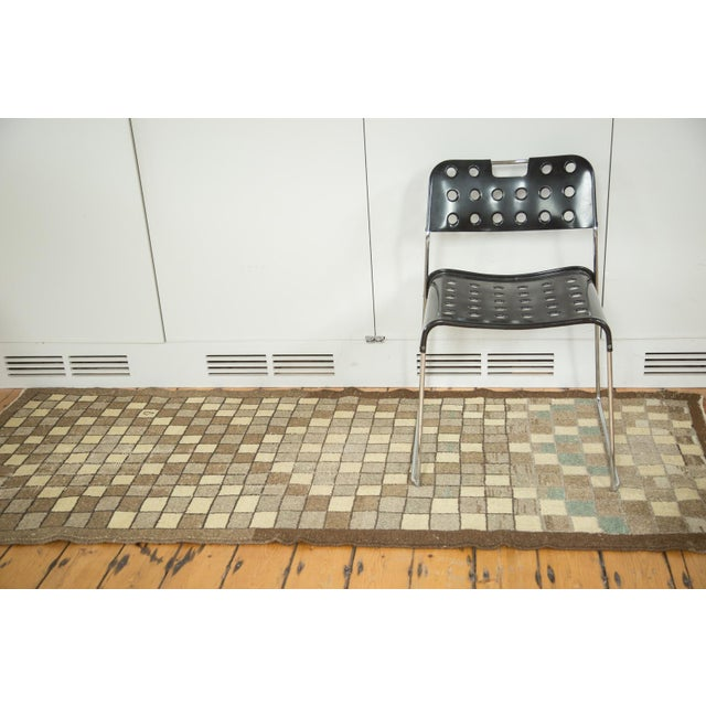Fun and funky checkered design rug runner with two and one partial stylized diamond design elements. Colors include ivory,...