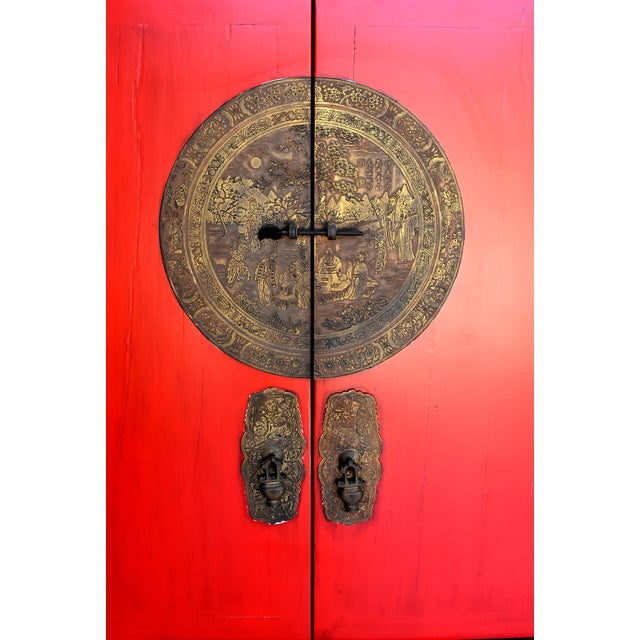 A traditional wedding cabinet from southern China. Bright red symbolizes good fortune, Golden brass medallion symbolizes...