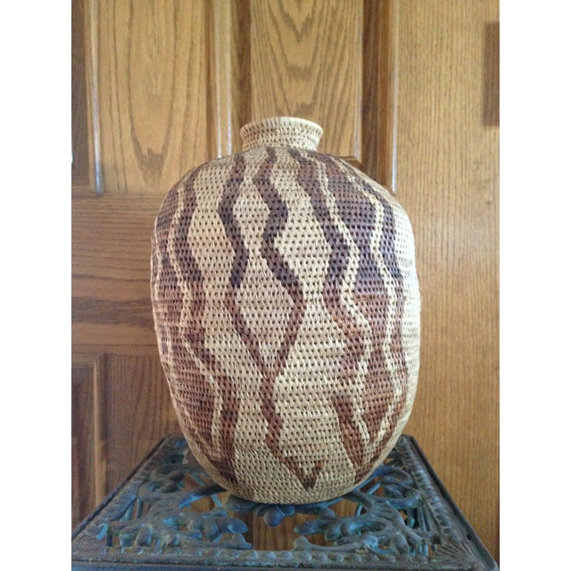 Beautifully hand-made tribal basket vase. It is in excellent condition and has no damage or discoloration. There are...